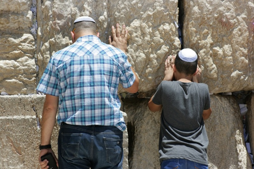 Men praying next to the Western Wall
